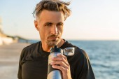 Fotografie handsome adult man with fitness bottle on seashore in front of sunrise