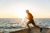 Photo sporty adult man in headphones doing one legged squats during training on seashore