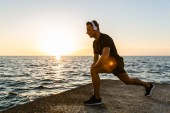 Fotografie athletic adult man in headphones doing one legged squats during training on seashore