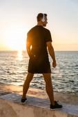 zadní pohled na atletické dospělé muže v sluchátka stojí na pobřeží před východem slunce