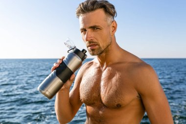 Shirtless wet adult man with fitness bottle of water on seashore stock vector