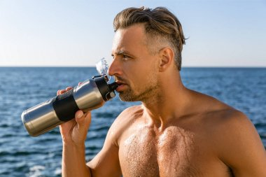 shirtless handsome adult man drinking water after workout on seashore