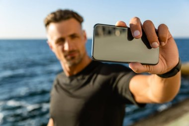 close-up portrait of adult man taking selfie with smartphone on seashore