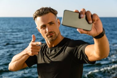 Handsome adult man taking selfie with smartphone and pointing at camera on seashore stock vector