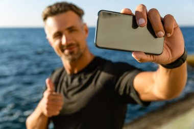 Close-up portrait of adult man taking selfie with smartphone and showing thumb up on seashore stock vector