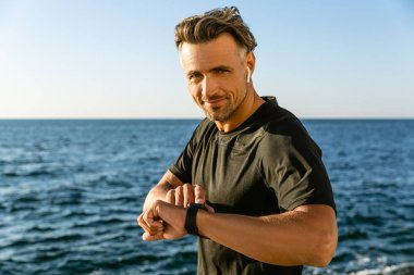 happy adult man with wireless earphones and smart watch on seashore