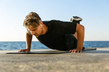 fit adult man with wireless earphones doing push ups on knees on seashore