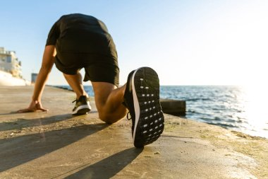 sporty sprint runner in start position for run on seashore