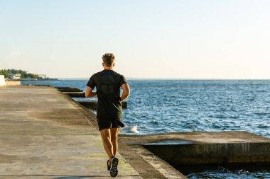 handsome adult sportsman running on seashore