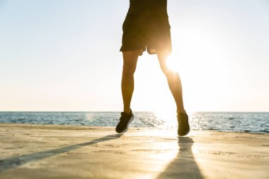 handsome adult sportsman jumping on seashore
