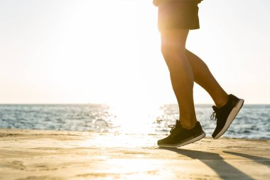 cropped shot of sportsman jogging on seashore in front of sunrise