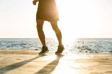cropped shot of fit man jogging on seashore in front of sunrise