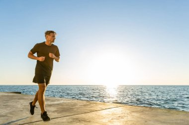 Handsome adult sportsman jogging on seashore in front of sunrise stock vector