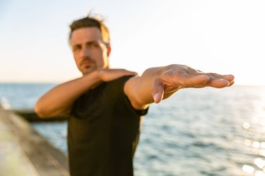 close-up shot of adult sportsman stretching arm before training on seashore