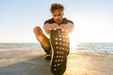 sporty adult man stretching leg on seashore in front of sunrise