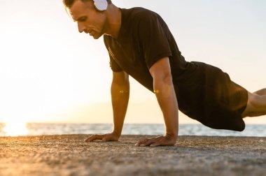 athletic adult man in headphones doing push ups on seashore