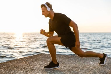 side view of handsome adult sportsman in headphones doing lunges during training on seashore