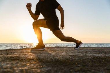 deniz kıyısı eğitim sırasında lunges yapan atletik erkek kadeh kırpılmış
