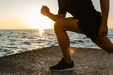 cropped shot of sportsman doing lunges during training on seashore in morning