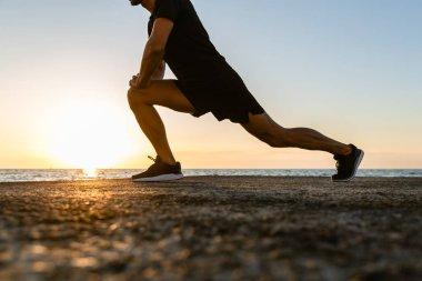 cropped shot of sportsman doing lunges during training on seashore