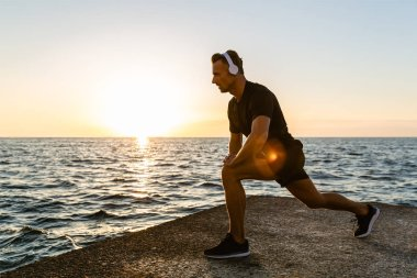 athletic adult man in headphones doing one legged squats during training on seashore