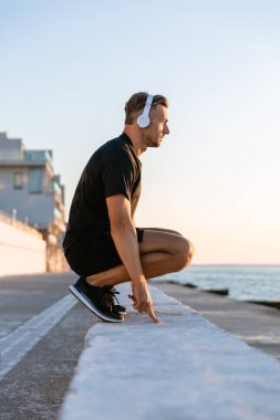 side view of handsome adult sportsman in headphones standing squats on parapet on seashore
