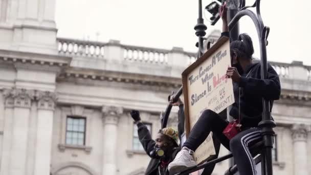 Londýn / UK - 06 / 06 / 2020: Black Lives Matter protest během uzamčení koronavirové pandemie. Ženské protestantky sedící na podzemní ceduli s praporem.