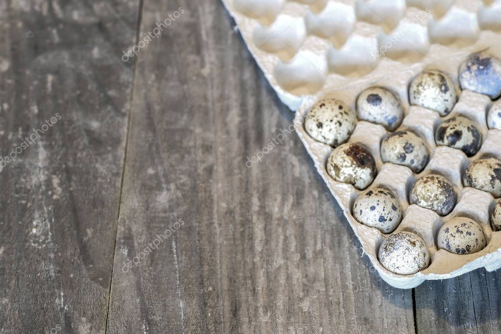 Quail eggs in a paper cast container in the form of a tray on a wooden vintage background. The concept of healthy eating benefits.