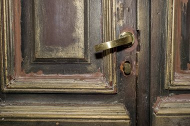 Part of a 17th century wooden door with brass handle. Background