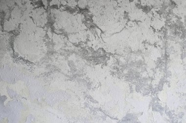 A gray concrete wall with a vertical lighting gradient intersper