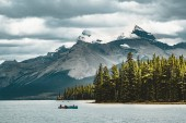 Fotografie a canoe on maligne lake in summer with a backdrop of the canadian rockies in jasper national park, alberta, canada