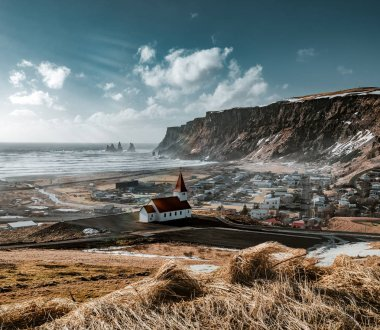 Panoramic view of the Vik at sunrise sunset . South Iceland.Typical red colored wooden church in Vik town, Iceland in winter.. Photo taken in Iceland. stock vector