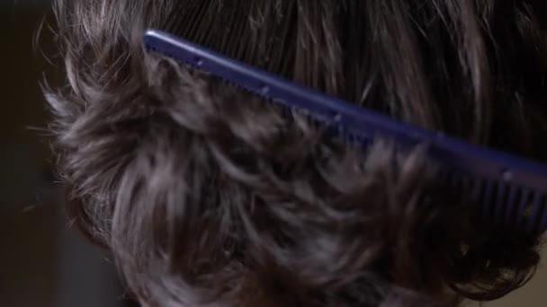Vlasy textury pozadí, žádná osoba. Černé lesklé kudrnaté vlasy hřebenem texturte. 4k, zpomalené. detail