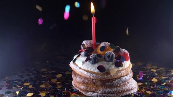 dovolená, oslava a strana koncept - narozeniny cupcake s jeden hořící svíčky na černém pozadí, konfety. Konfety na oslavu. Super slow motion