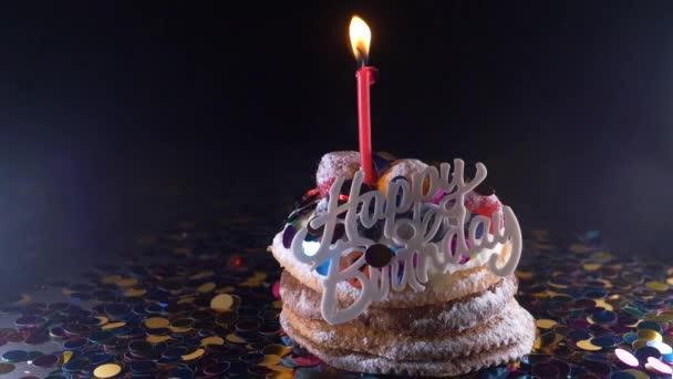 ünnep, az ünneplés és a fél fogalma - birthday cupcake egy égő gyertya felett a fekete háttér, konfetti. Konfetti a párt. Super slow motion