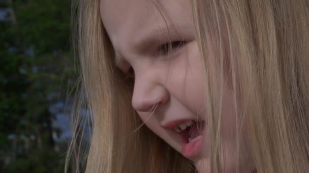 Nahaufnahme Porträt, Gesicht des kleinen Mädchens, das draußen spielt, müdes Kind, das in die Kamera schaut, 4k,