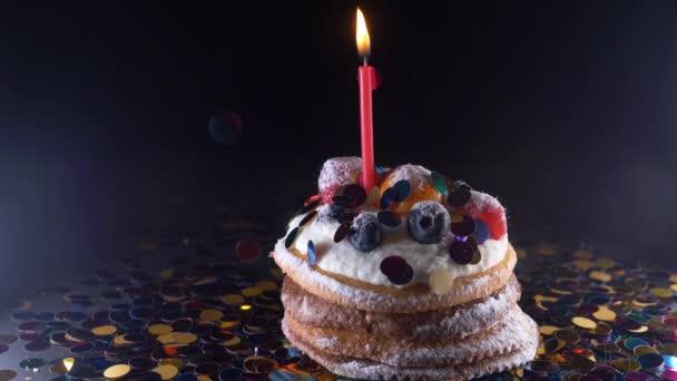 concetto di partito, di celebrazione e di festa - bigné di compleanno con una masterizzazione candele sopra priorità bassa nera, coriandoli. Confetti per una festa. Super slow motion.