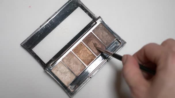 Female hand eye shadow tassel on white background isolation. 4k, slow motion