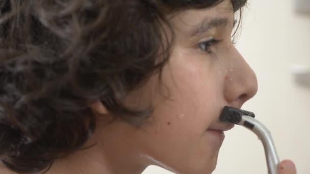 Tinédzser leborotválja először, tizenéves fiú alkalmazása borotvahab, bőrápoló, krém, arc, 4k, közeli