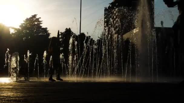 Childrens silhouettes play in the citys fountain on a summer day. 4k.