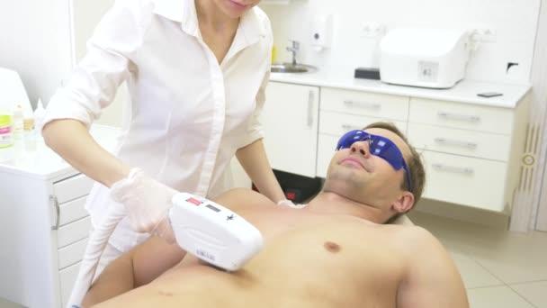 männliche Laser-Haarentfernung. Ein Arzt in weißen Handschuhen entfernt einem Mann die Haare aus Bauch und Brüsten. 4k, Nahaufnahme. Zeitlupe
