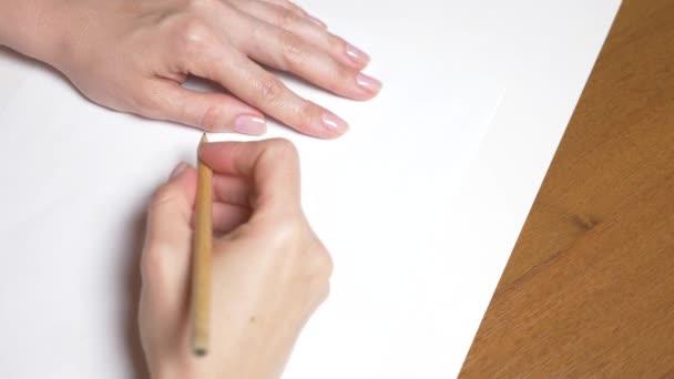 Lassú mozgás. 4k, közeli, felülnézet. egy női kéz rajzol egy ceruzával. rajza egy lányt a ruha