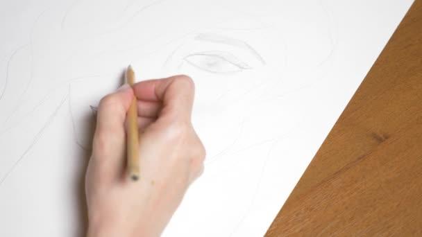 egy női kéz rajzol egy portré egy lány. 4k, zár-megjelöl. Lassú mozgás. Nézd meg felülről.