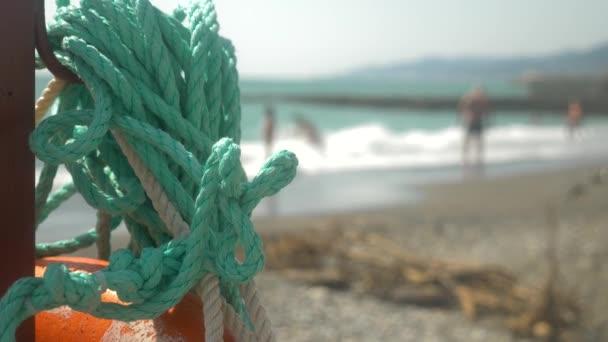 detail. moře uzel na záchranný kruh na veřejné pláži. siluety lidí. Slunce, opalování, plavání, pěší turistika, odpočinek a relaxaci. 4k, pomalý pohyb