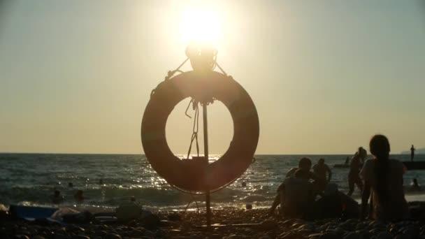 Záchranný kruh na na veřejné pláži. siluety lidí. Slunce, opalování, plavání, Turistika, odpočinek a relaxaci