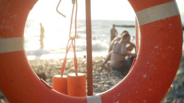Rettungsring an einem öffentlichen Strand. Silhouetten von Menschen. Sonnenbräune, Schwimmen, Tourismus, Erholung und Entspannung