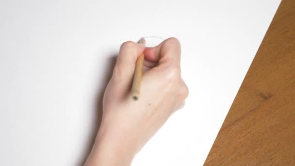 ženská ruka nakreslí portrét dívky. 4k, detail. Zpomalený pohyb. pohled shora.