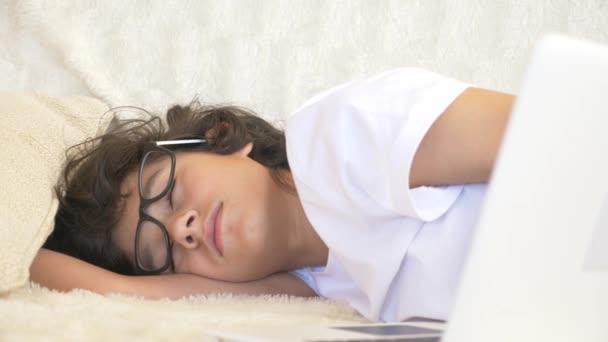 szemüveg viselése Aranyos fiú tinédzser alszik a kanapén laptop mellett. 4k
