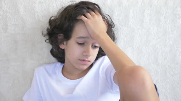 portrét smutný unavený dospívající chlapec, který sedí na gauči. 4k