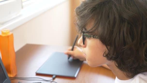 pohledný moderní chlapec dospívající pracuje na grafickém tabletu. on se dívá na obrazovku notebooku. 4k, pomalý pohyb